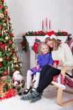 Christmas or New year celebration. Happy mother and daughter sitting in chair near Christmas tree with xmas gifts. A fireplace wit Stock Image