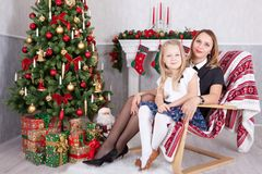 Christmas or New year celebration. Happy mother and daughter sitting in chair near Christmas tree with xmas gifts. A fireplace wit Stock Photography