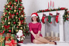 Christmas or New year celebration. Happy woman in red dress sitting near Christmas tree with xmas gifts. A fireplace with christma Royalty Free Stock Image