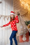 Christmas or New Year celebration. Happy woman in the Santa Claus hat. looking at the camera. holding a bag with gifts Stock Photo