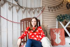 Christmas or New Year celebration. Happy woman sitting in the rocking chair. looking at the camera Royalty Free Stock Images