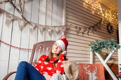 Christmas or New Year celebration. Happy woman sitting in the rocking chair. looking at the camera. the Santa Claus hat Royalty Free Stock Photography