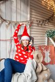 Christmas or New Year celebration. Happy woman sitting in the rocking chair. looking at the camera. the Santa Claus hat Stock Photos