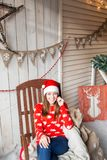 Christmas or New Year celebration. Happy woman sitting in the rocking chair. looking at the camera. the Santa Claus hat Royalty Free Stock Images