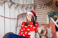 Christmas or New Year celebration. Happy woman sitting in the rocking chair. looking off to the side. the Santa Claus Stock Photos