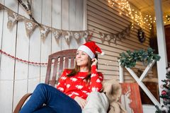 Christmas or New Year celebration. Happy woman sitting in the rocking chair. looking off to the side. the Santa Claus Stock Image