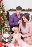 Christmas or New year celebration. Happy young family sitting in chair near Christmas tree with xmas gifts. A fireplace with chris Royalty Free Stock Images