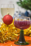 Christmas and New Year celebration holiday clock with two glasse. S of red and white wine and red ball covered with yellow fir on the red table Stock Photography