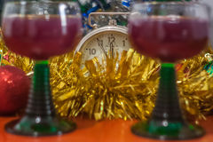 Christmas and New Year celebration holiday clock with two glasse. S of red wine and red ball covered with yellow fir on the red table Royalty Free Stock Image