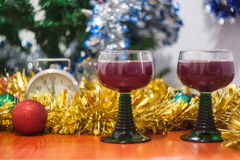 Christmas and New Year celebration holiday clock with two glasse. S of red wine and red ball covered with yellow fir on the red table Royalty Free Stock Photos