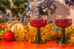 Christmas and New Year celebration holiday clock with two glasse. S of red wine and red ball covered with yellow fir on the red table Stock Images