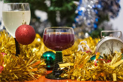 Christmas and New Year celebration holiday clock with two glasse. S of red wine and red ball covered with yellow fir on the red table Stock Photo