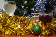 Christmas and New Year celebration holiday clock with two glasse. S of wine and red ball covered with yellow fir on the red table Royalty Free Stock Image