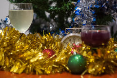 Christmas and New Year celebration holiday clock with two glasse. S of wine and red ball covered with yellow fir on the red table Stock Image