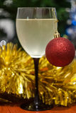 Christmas and New Year celebration holiday clock with two glasse. S of wine and red ball covered with yellow fir on the red table Royalty Free Stock Images