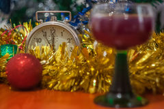 Christmas and New Year celebration holiday with glass of wine an. D red ball covered with yellow fir on the red table Royalty Free Stock Photos