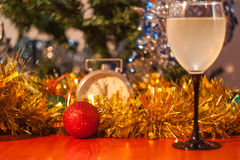 Christmas and New Year celebration holiday with glass of wine an. D red ball covered with yellow fir on the red table Royalty Free Stock Photography