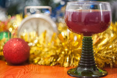 Christmas and New Year celebration holiday with glass of wine an. D red ball covered with yellow fir on the red table Stock Photo