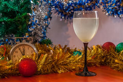 Christmas and New Year celebration holiday with glass of wine an. D red ball covered with yellow fir on the red table Stock Photography