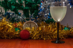 Christmas and New Year celebration holiday with glass of wine an. D red ball covered with yellow fir on the red table Stock Images