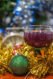 Christmas and New Year celebration holiday with glass of wine an. D red ball covered with yellow fir on the red table Stock Photos