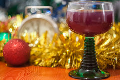 Christmas and New Year celebration holiday with glass of wine an. D red ball covered with yellow fir on the red table Royalty Free Stock Image