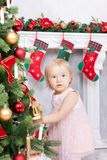 Christmas or New year celebration. Little girl in cute pink dress decorating Christmas tree at home near the fireplace with christ Stock Photos