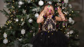 Little girl blowing Christmas confetti. Christmas and New Year celebration. Little girl having fun on holiday blowing colorful confetti stock video