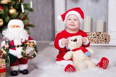 Christmas or New year celebration. Little girl in red dress and santa hat with bear toy sitting on the floor near the Christmas tr. Ee with xmas gifts. A royalty free stock image