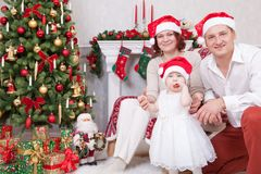 Christmas or New year celebration. Portrait of cheerful young family of three people near the Christmas tree with xmas gifts. A fi royalty free stock photos