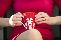 Christmas or New year celebration. The woman in a red dress keeps a Christmas mug with a deer. Closeup Royalty Free Stock Photo