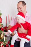 Christmas or New year celebration. The young beautiful father holds the little daughter on hands dressed in red festive suit of gn. Christmas or New year royalty free stock image