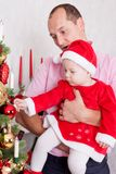 Christmas or New year celebration. The young beautiful father holds the little daughter on hands dressed in red festive suit of gn. Christmas or New year royalty free stock photo