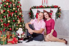 Christmas or New year celebration. Young couple sit and embrace in Christmas interior, near the fireplace, Christmas tree. Happy h Royalty Free Stock Photography