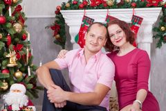 Christmas or New year celebration. Young couple sit and embrace in Christmas interior, near the fireplace, Christmas tree. Happy h Stock Images