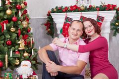 Christmas or New year celebration. Young couple sit and embrace in Christmas interior, near the fireplace, Christmas tree. Happy h Stock Photo