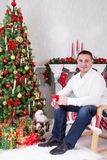Christmas or New year celebration. Young man sits in a armchair and holds a cup near Christmas tree with xmas gifts. A fireplace w. Ith christmas stocking on Stock Image