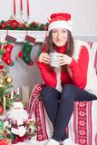 Christmas or New year celebration. Young woman in a red jumper, fur vest and Santas hat, holds a cup in hand and sitting in a chai Royalty Free Stock Image