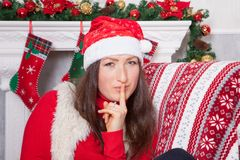 Christmas or New year celebration. Young woman in a red jumper, fur vest and Santas hat, sits in a chair in a Christmas interior, Stock Images