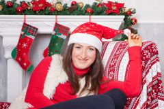 Christmas or New year celebration. Young woman in a red jumper, fur vest and Santas hat, sits in a chair in a Christmas interior, Stock Photography