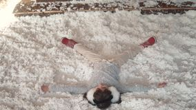 Christmas or New Year. child is making an angel lying on the snow. little girl fools around and lies in artificial snow. Christmas or New Year. Children in light stock video