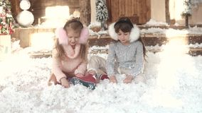 Christmas or New Year. children in fur headphones are sitting on artificial snow. portrait of two little girls. sisters. Christmas or New Year. a little girl stock footage