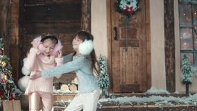 Christmas or New Year. Children in light winter clothes give each other hugs. Two little girls on the porch of the house.  stock video