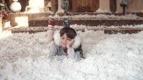 Christmas or New Year. child fools around and lies in artificial snow. portrait of a child in Christmas decorations. Christmas or New Year. Children in light stock footage