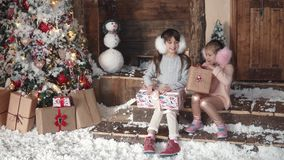 Christmas or New Year. children are looking at presents in beautiful Christmas boxes. two little girls on a christmas. Christmas or New Year. a little girl stock footage