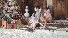 Christmas or New Year. children are looking at presents in beautiful Christmas boxes. two little girls on a christmas. Christmas or New Year. a little girl stock video footage