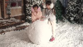 Christmas or new year. children make a snowman. two little girls make a ball of snow. Christmas or New Year. a little girl hanging decorations on a Christmas stock video