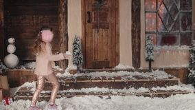 Christmas or New Year. children playing snowballs on the porch of the house. two little sisters are having fun and. Christmas or New Year. Children in light stock video