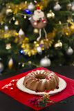 Christmas or New Year chocolate cake with powdered sugar on the top, fresh red berries on white porcelain plate. On red tablecloth and wooden figurine of deer royalty free stock photos