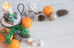 Christmas or New Year composition with a candle, tangerines, and Christmas decorations, pine cones, a place for text. holiday royalty free stock image